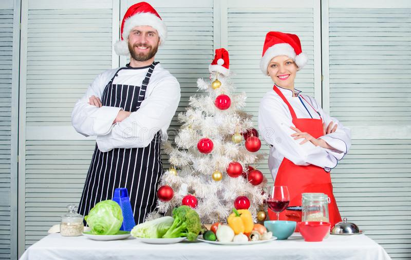 Secret ingredient is love. Couple preparing a healthy meal together for christmas dinner. Man and woman chef apron santa royalty free stock image