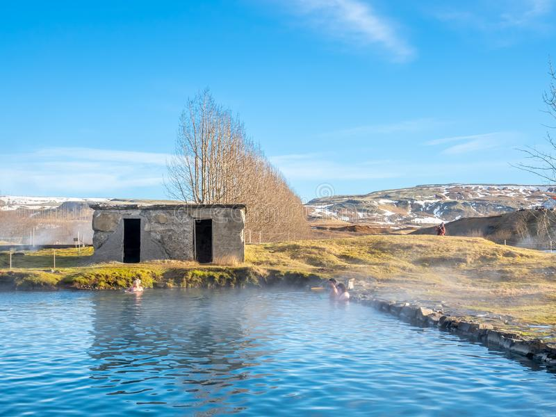 Secret lagoon hot spring in Fludir, Iceland. FLUDIR, ICELAND - MARCH 6 : Secret lagoon hot spring, public outdoor warming swimming pool, landmark of small city royalty free stock photo