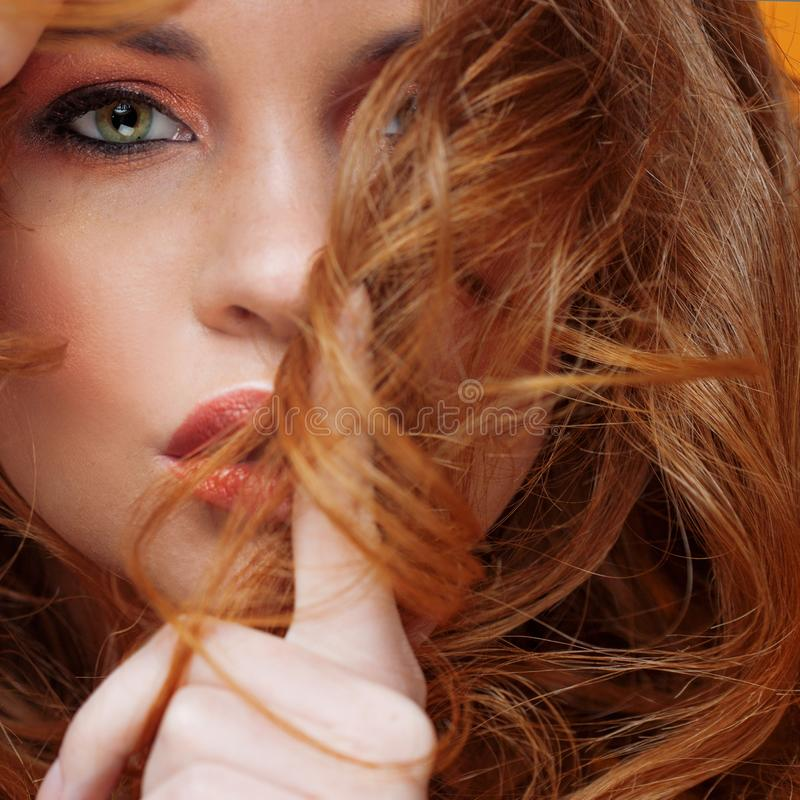 The secret of luxurious hair. Beautiful red-haired woman, finger at the lips, curls stock photo