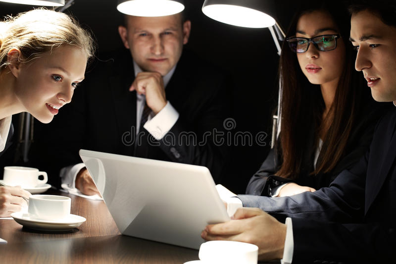 Secret project. Manager showing his project to his colleagues at night meeting royalty free stock photo