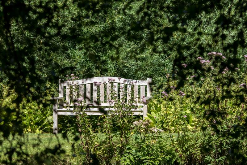 Secret rendezvous. Secluded empty bench seat in a country garden royalty free stock images