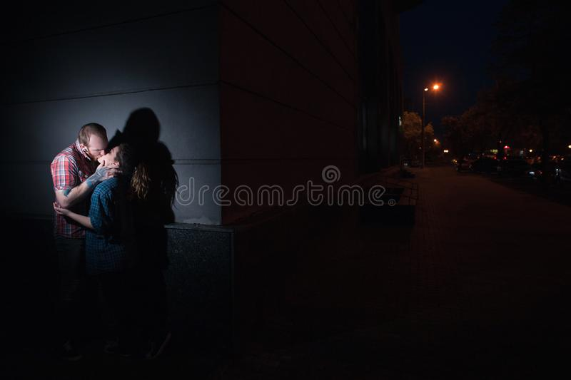 Secret romantic date at night. Kissing couple. Forbidden relationships, adultery, dark street background, atmospheric light, prohibitive concept stock image