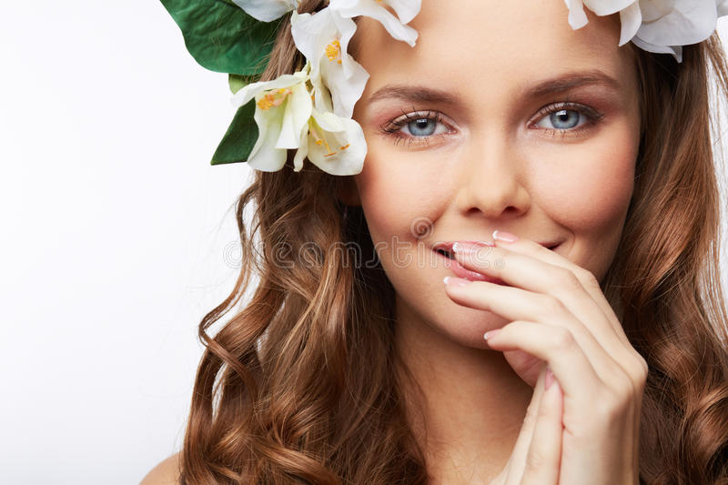 Secret smile. Close-up portrait of a gorgeous girl with flower hairstyle covering her smile with her hand stock photos