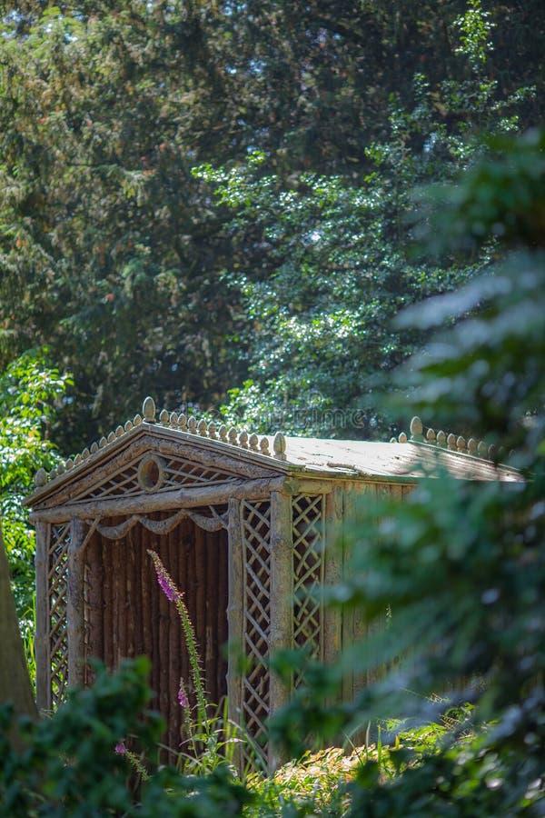 Secret summer house. Ornamental wooden trellis garden gazebo sea. Ting area. Beautiful garden retreat stock photos