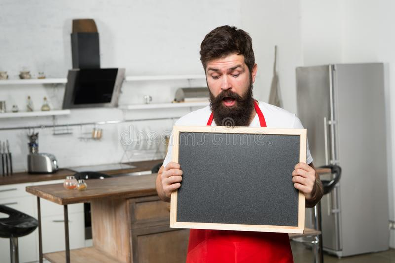 Secret tips. Useful information. Man bearded hipster red apron stand in kitchen. Kitchen furniture store. Kitchen hacks stock photography