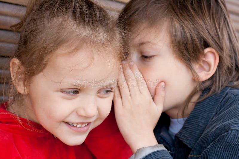 Secret. Two kids sharing a secret royalty free stock image