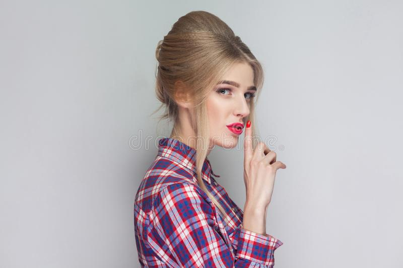 This is secret between us. beautiful girl in pink checkered shirt, collected updo hairstyle and makeup standing and looking at ca royalty free stock photo
