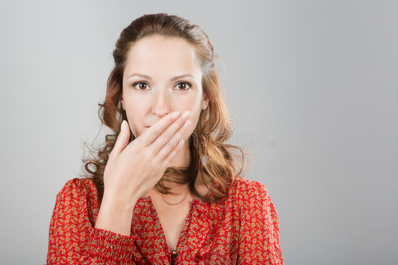 Secret woman saying be quiet. Girl with hand in front of mouth. shut up.In red blouse. Grey background. Studio shot stock images