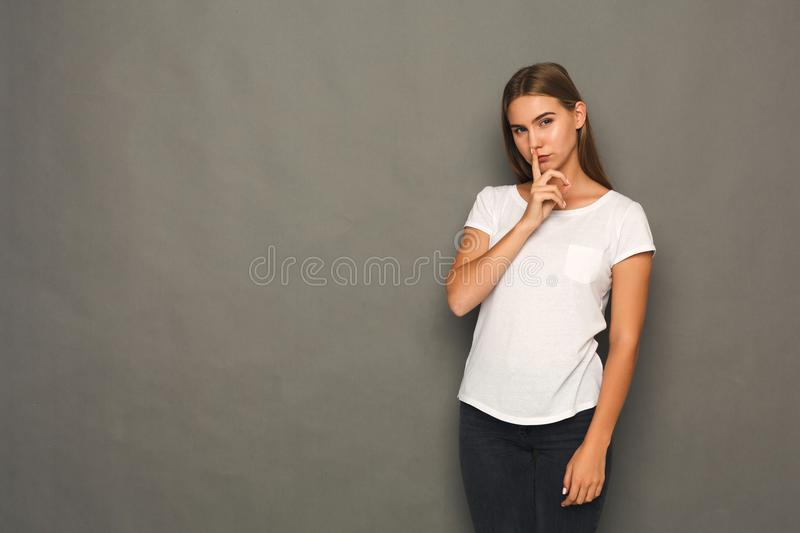Secret. Young woman put finger on lips, hush sign royalty free stock photo