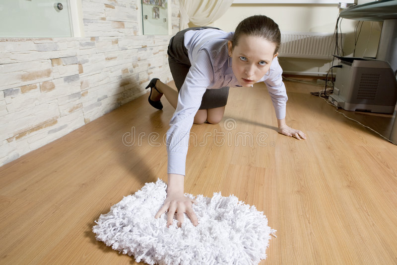 Secretaresse die de vloer in bureau wast stock afbeelding