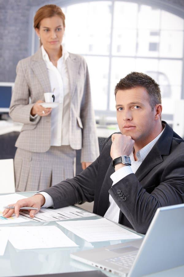 Secretaresse die jonge werkgever met koffie dient stock foto's