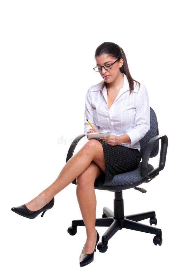 Secretaresse die op een bureaustoel wordt gezeten die nota's neemt. stock foto's