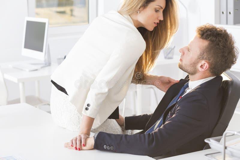 Secretaresse die provocatively over de man op het werk leunen stock afbeeldingen