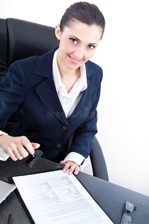 Secretaresse die zegel op document zet stock foto's
