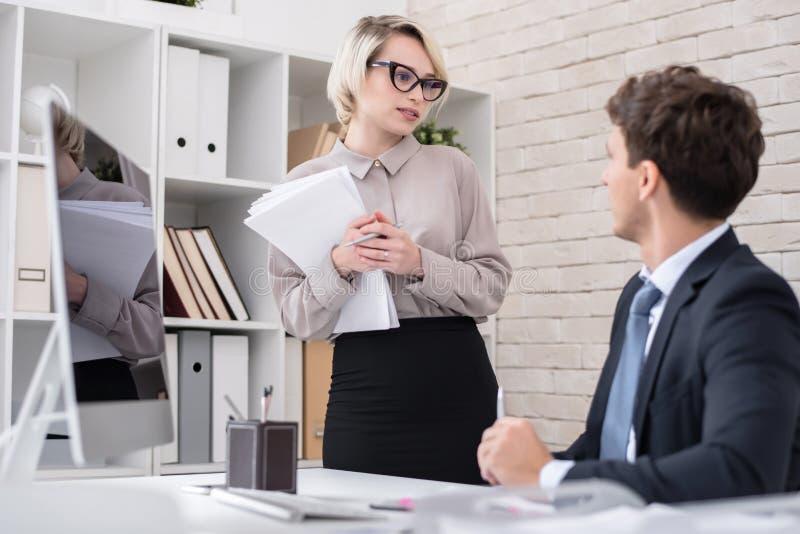 Secretaresse Talking aan Werkgever in Bureau stock afbeelding