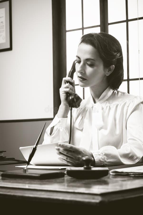 Secretaria atractiva del vintage en el teléfono imágenes de archivo libres de regalías