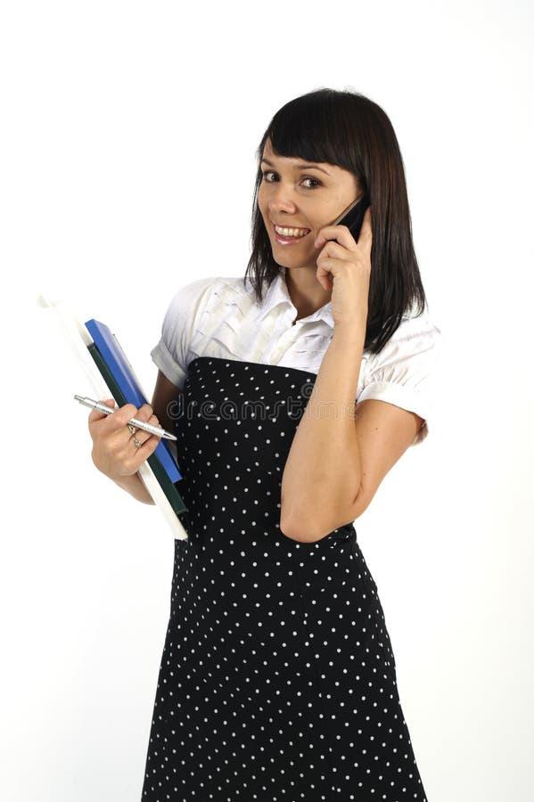 Secretaria atractiva que usa el teléfono móvil fotografía de archivo