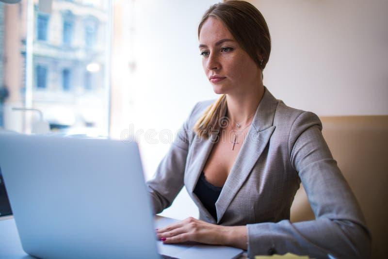 Secretaria de la mujer joven que comprueba el email en el ordenador portátil durante día del trabajo en empresa fotografía de archivo