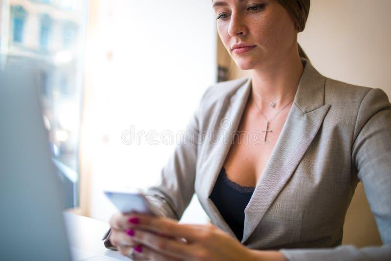 Secretaria de la mujer usando los apps en el teléfono de célula mientras que se sienta con el dispositivo del cuaderno en espacio fotos de archivo libres de regalías
