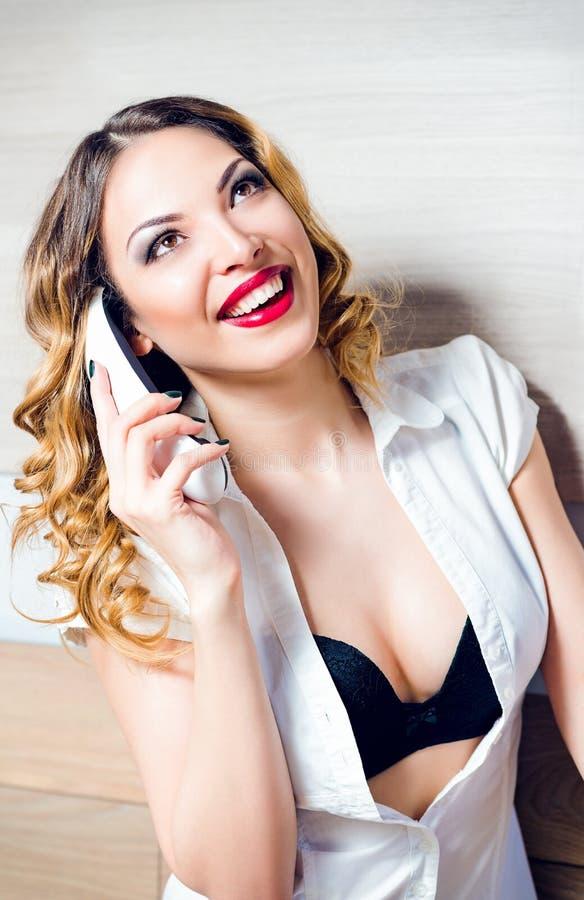 Secretaria de risa bonita que habla en el teléfono fotografía de archivo