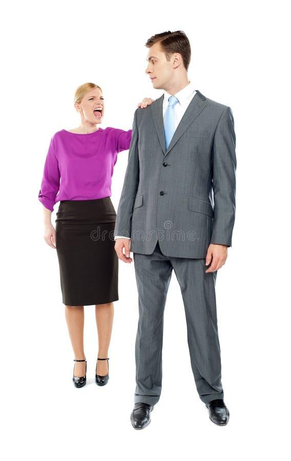 Secretaria de sexo femenino que grita en su compañero de trabajo imagen de archivo