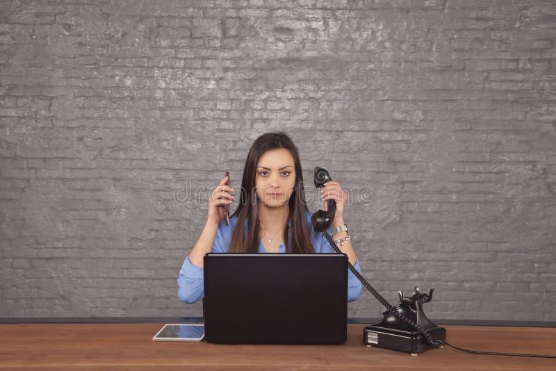 Secretaria hermosa joven para conducir dos llamadas de teléfono al mismo tiempo fotos de archivo