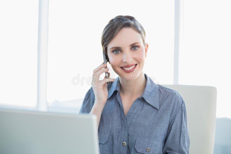 Secretaria joven amistosa que llama por teléfono con su smartphone que se sienta en su escritorio imagen de archivo