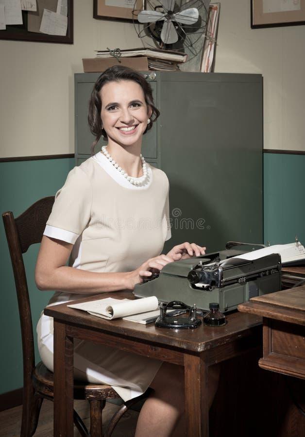 Secretaria joven del vintage en el trabajo fotos de archivo