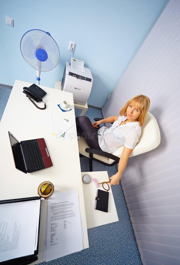 Secretaria joven en lugar de trabajo en la oficina fotografía de archivo