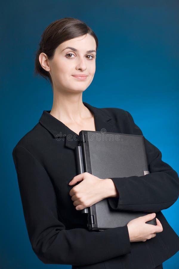Secretaria o empresaria en juego con el cuaderno en fondo azul foto de archivo