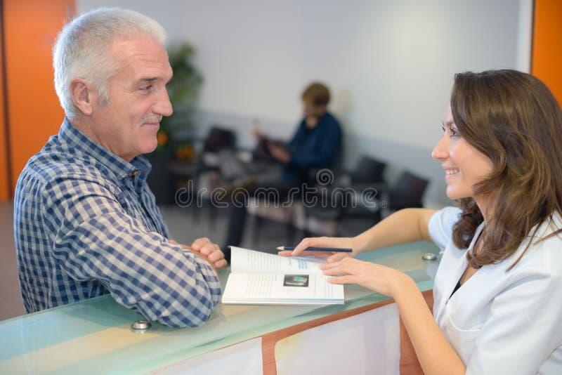 Secretaria que muestra el folleto al hombre imagenes de archivo