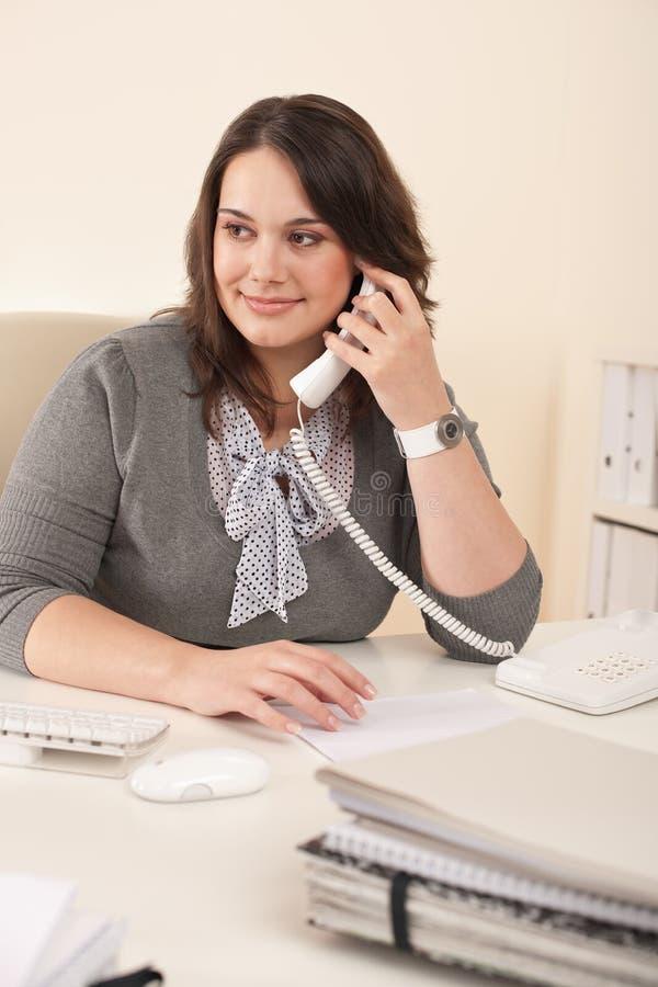 Secretaria sonriente en el teléfono en la oficina fotografía de archivo