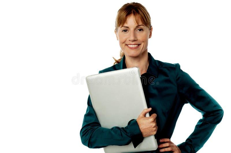 Secretaria sonriente que sostiene el ordenador portátil imágenes de archivo libres de regalías
