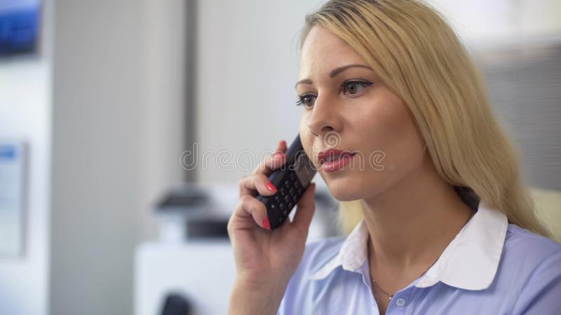 Secretary answering phone call and talking to clients in office, business stock photos