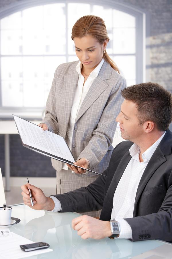 Secretary bringing contract to sign to boss stock images