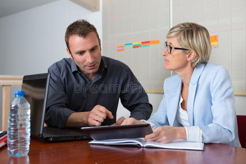 Secretary helping boss with tablet in office royalty free stock images