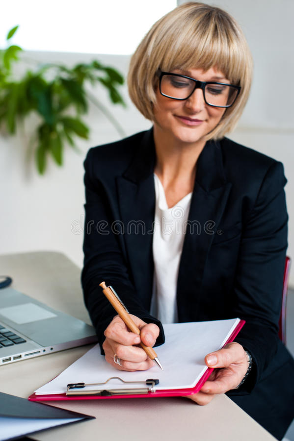 Secretary jotting down notes and instructions. Secretary at work jotting down notes and instructions from her boss stock photos