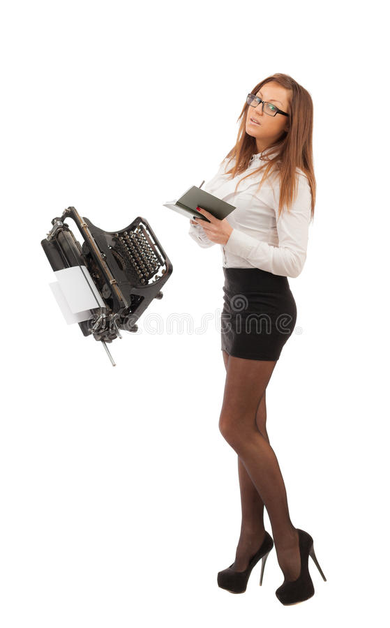 Secretary with long legs. A notebook and a typewriter on a white background royalty free stock images