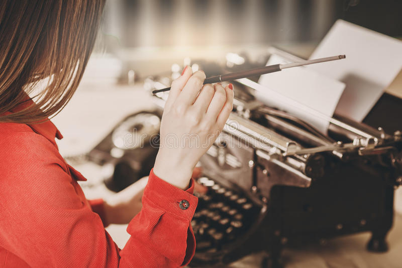 Secretary at old typewriter with telephone. Young woman using ty. Pewriter. Business concepts. Retro picture style royalty free stock image
