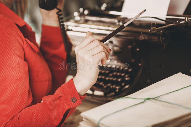 Secretary at old typewriter with telephone. Young woman using ty. Pewriter. Business concepts. Retro picture style stock photo