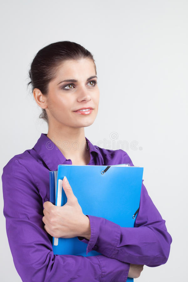Secretary with plastic folders. Pretty young brunette woman holding colorful plastic folders stock photo