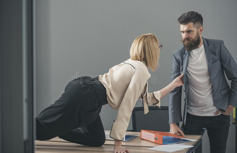 Secretary pulls jacket of boss in office, seduction and flirting concept.  stock images