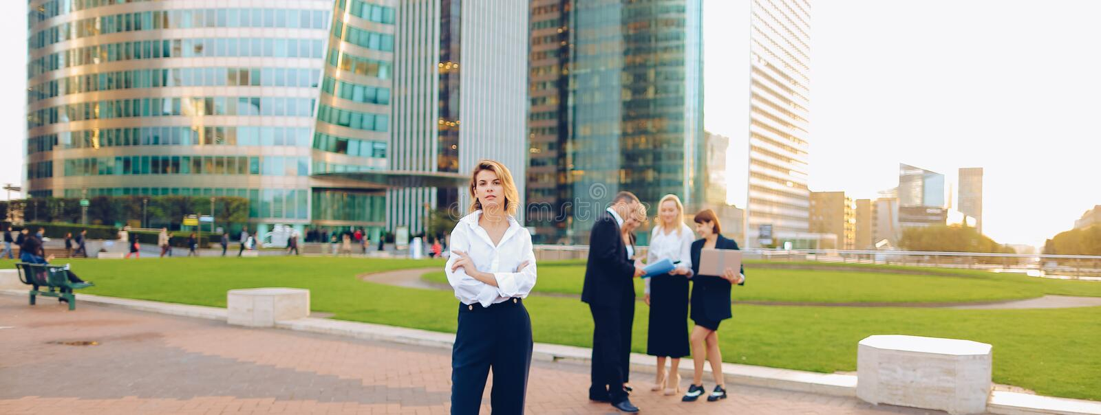 Secretary looking at camera with team members background in La D stock image