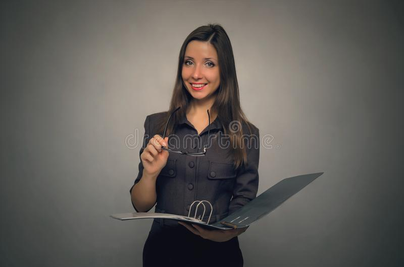 Secretary or teacher woman. Beautiful smiling young woman holding in hands the open folder with documents. Secretary. Documentation work stock images