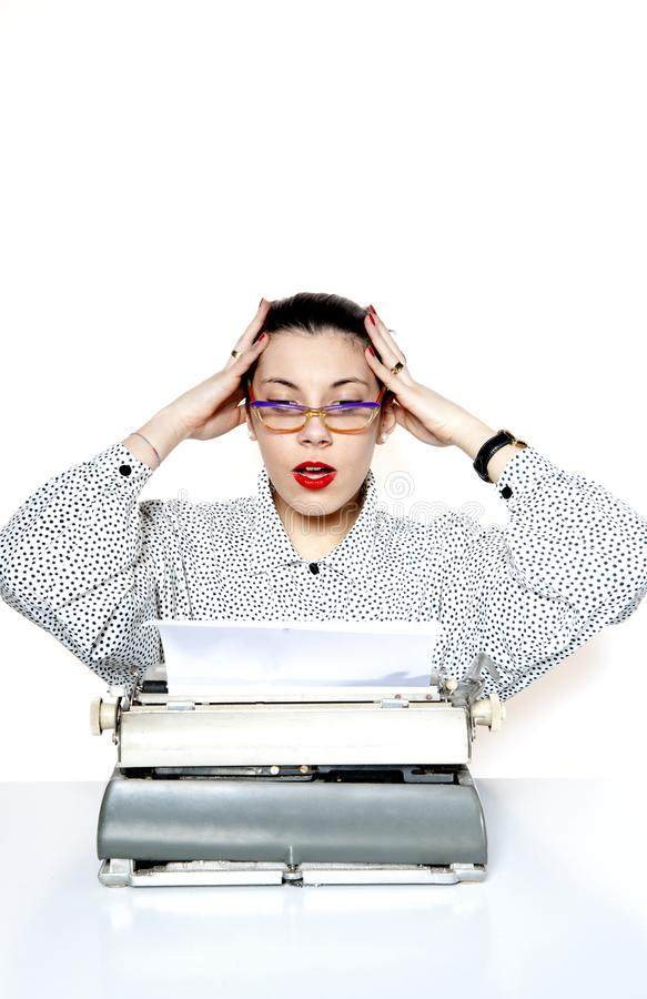 Portrait of a desperate secretary, or a teacher, with a vintage typewriter. Portrait of a secretary or a teacher with glasses and red nails with a vintage stock photos