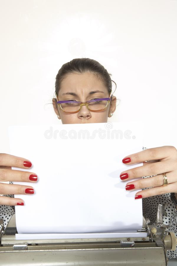 Portrait of a secretary, or a teacher, with a vintage typewriter. Portrait of a secretary or a teacher with glasses and red nails with a vintage typewriter royalty free stock photos