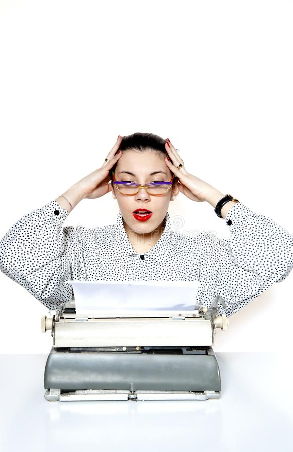 Portrait of a desperate secretary, or a teacher, with a vintage typewriter. Portrait of a secretary or a teacher with glasses and red nails with a vintage royalty free stock images
