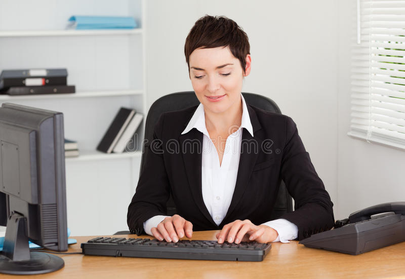 Secretary typing on her keybord. In her office stock images