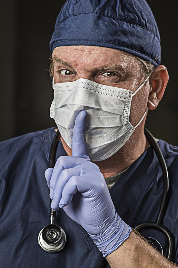 Secretive Doctor Wearing Protective Head Wear. Secretive Doctor or Nurse With Finger in Front of Mouth wearing Protective Wear and Stethoscope royalty free stock photo