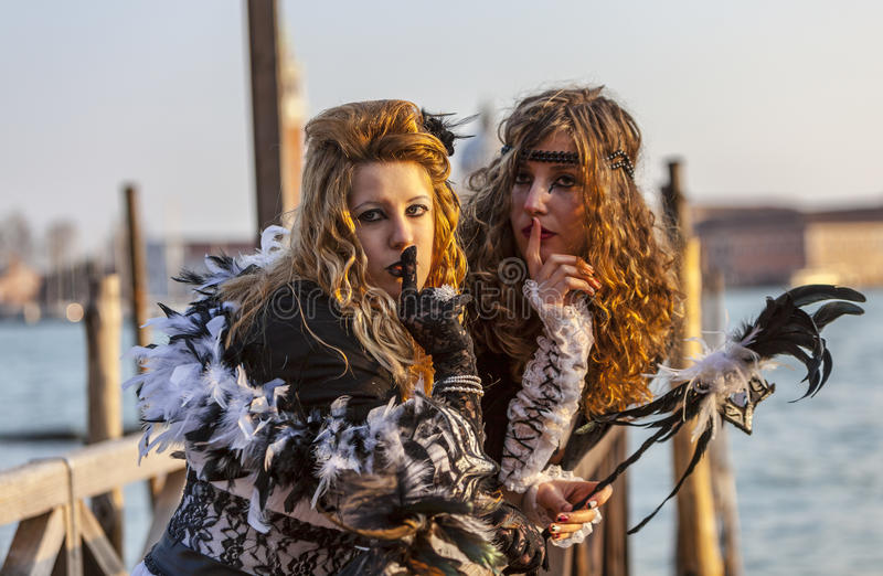 Secretive Women. Venice, Italy-February 18,2012: Portrait of two young women with a secretive attitude posing near the gondola's dock in San Marco Square in royalty free stock images